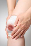 Injured knee with bloody bandage Stock Images
