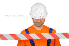 Injured laborer at accident scene hard hat with blood and warning tape on white Stock Image