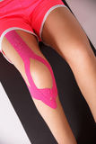Injured leg with kinesio tape Stock Images