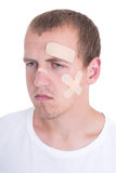 Injured man with adhesive plaster on his face Royalty Free Stock Photo