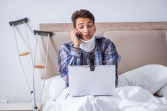 The injured man chatting online via webcam in bed at home Royalty Free Stock Photography