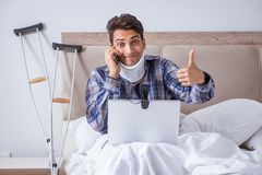 The injured man chatting online via webcam in bed at home Stock Photography