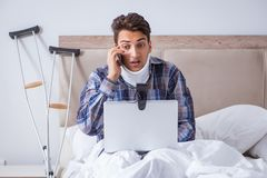 The injured man chatting online via webcam in bed at home Stock Photo