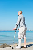 Injured Man with Crutches at sea side Royalty Free Stock Images