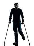 Injured man with crutches silhouette Royalty Free Stock Images