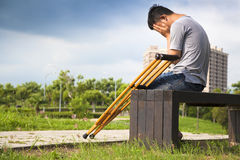 Injured Man with crutches sitting on a bench Royalty Free Stock Photo