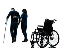 Injured man  with crutches   with woman  walking away from  whee. One men injured men with women walking away from wheelchair with crutches in silhouette studio Royalty Free Stock Image