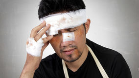 Injured man expressing head trauma concept. Close up expression of a man with bruised and bandaged face feels traumatic head pain. Conceptual image of accident Royalty Free Stock Photos