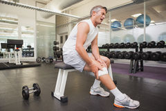 Injured man gripping his knee in the weights room Royalty Free Stock Photo