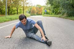Injured man has broken leg and is sitting on road Royalty Free Stock Photos