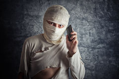 Injured Man with Head Bandages using Mobile Phone Royalty Free Stock Photo