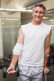 Injured man holding dumbbell in the weights room Royalty Free Stock Photo