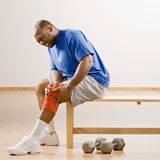 Injured man holding knee splint. In health club stock photography