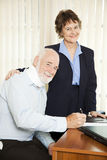 Injured Man with Lawyer. Injured senior man signing paperwork in his attorney's office royalty free stock image