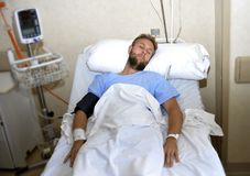 Injured man lying in bed hospital room resting from pain looking in bad health condition. Young injured patient man lying in bed hospital room resting from pain Royalty Free Stock Photos