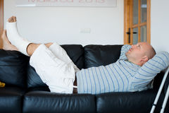 Injured Man Lying on Sofa Stock Image