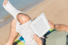 Injured Man relaxing on the beach. And reading a book on tablet pc stock image