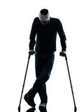Injured man standing with crutches silhouette Royalty Free Stock Photography