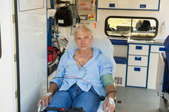 Injured man on stretcher in ambulance car. Injured senior man sitting on stretcher in ambulance car royalty free stock photos