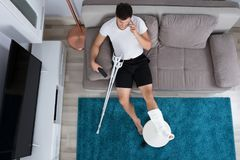 Injured Man Talking On Mobile Phone. High Angle View Of Young Man With Broken Leg Talking On Mobile Phone stock photography
