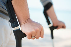 Injured Man Trying to walk on Crutches. At a beach Royalty Free Stock Images