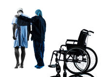 Injured man walking away from  wheelchair with nurse silhouette Stock Images