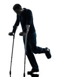 Injured man walking with crutches silhouette Royalty Free Stock Images