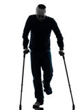 Injured man walking with crutches silhouette Royalty Free Stock Photography