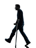 Injured man walking with crutches silhouette Royalty Free Stock Photos