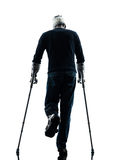 Injured man walking  rear view with crutches silhouette Royalty Free Stock Image
