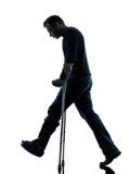 Injured man walking sad with crutches silhouette Stock Image