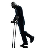 Injured man walking sad with crutches silhouette Stock Photos