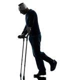 Injured man walking sad with crutches silhouette Stock Photos
