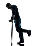 Injured man walking sad with crutches silhouette Royalty Free Stock Photography