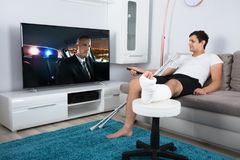Injured Man Watching Television stock photography