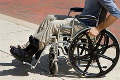 Injured Man Wheelchair. Injured man with a broken foot pushes himself along in his wheelchair stock photo