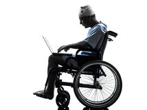 Injured man in wheelchair computing laptop computer silhouette Royalty Free Stock Photo