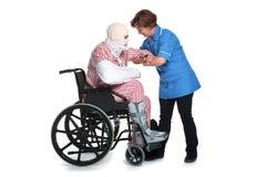 Injured man wheelchair with nurse lifting Stock Image