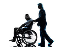 Injured man in wheelchair with nurse silhouette Stock Images