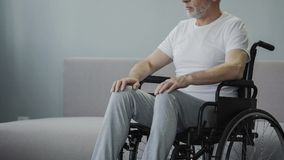 Injured man in wheelchair at rehabilitation center, hopes to walk again, closeup. Stock footage Stock Image