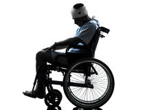 Injured man in wheelchair silhouette. One injured man in wheelchair sleeping in silhouette studio on white background stock photography