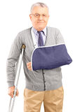 Injured mature man with broken arm walking with crutches. Isolated on white background stock photos