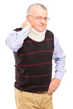 An injured mature man with neck holder suffering from a pain Royalty Free Stock Images
