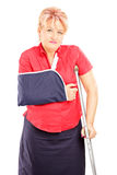 Injured mature woman with broken arm and crutch Stock Photography