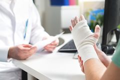 Injured patient showing doctor broken wrist and arm with bandage. In hospital office or emergency room. Sprain, stress fracture or repetitive strain injury in royalty free stock image