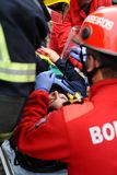 Life saving demonstration by firefigters. A injured person removed from interior of crash car with security equipement and firefighters straped her with care Stock Photo