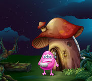An injured pink monster near the mushroom house Stock Image