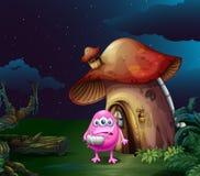 An injured pink monster near the mushroom house Stock Image