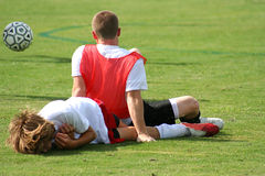 Injured Players. Two soccer players have collided and fallen  to the ground Stock Image