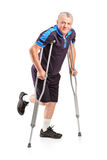 Injured senior player on crutches. Full length portrait of an injured senior player on crutches  on white background Royalty Free Stock Images
